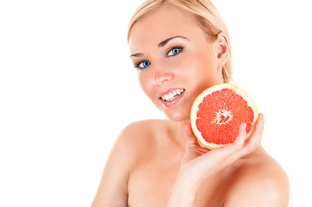 beautiful healthy woman with half a grapefruit in hands photo