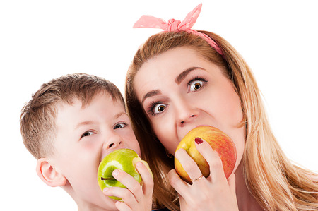 portrait of mother son cheerfully biting apple photo