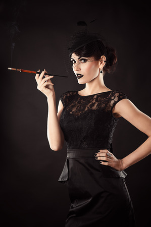 retro woman with a mouthpiece in a hand isolated on black photo