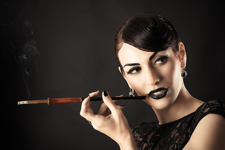 Beauty Retro Model with Black Makeup and mouthpiece in hand photo