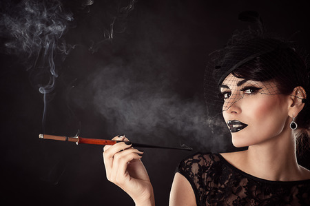 attractive woman with dark makeup with mouthpiece photo