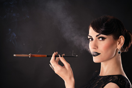 attractive woman with dark makeup smokes a cigarette photo