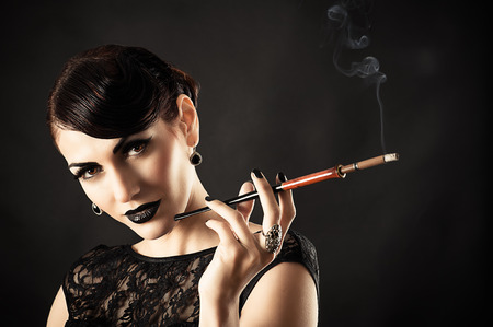 Beauty Retro Model with Black Makeup and Cigarette in hand photo