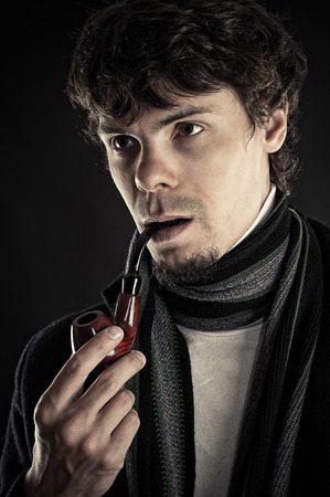 intelligent man with a pipe in a mouth isolated on black photo