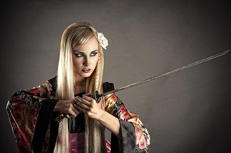 beautiful woman with samurai sword isolated on gray photo