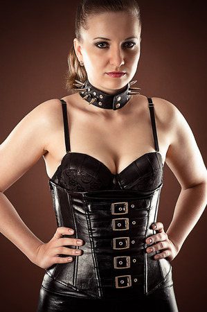 sadomasochism: beautiful woman in corset and spiked collar Stock Photo