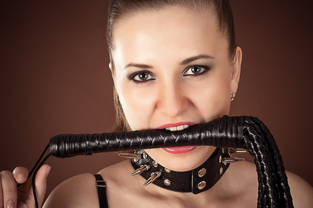 Portrait of mistress with a whip in the mouth Stock Photo