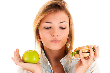 beautiful woman choosing between apple and hamburger photo