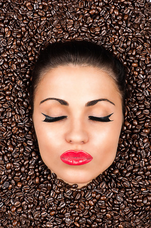 beautiful woman face with closed eyes in the coffee beans photo