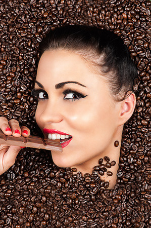 attractive woman in a coffee beans with chocolate in hand photo