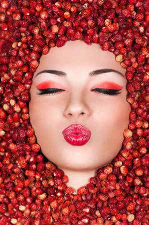 Beautiful woman lying in wild strawberry and air kiss photo