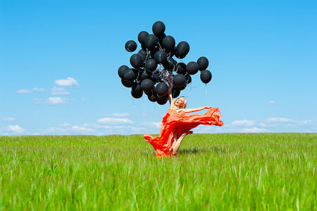 beautiful woman jumping with black balloons in hands photo