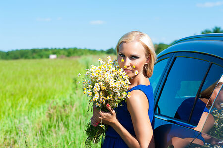 woman with daisies in hands standing near the car photo