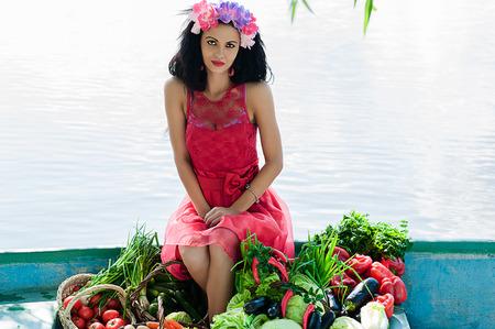 mujer elegante: elegante mujer sentada en un barco con verduras