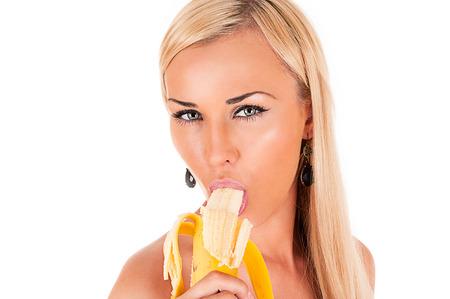 セクシーな魅力的な金髪の女性はバナナを食べる