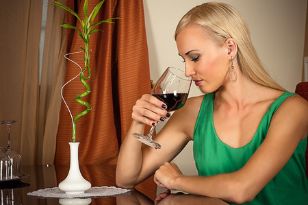 beautiful woman smelling a wine in a glass photo