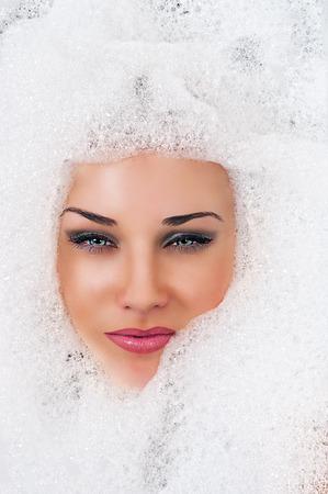 fashion beautiful blond woman face in the foam photo