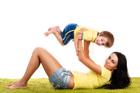 happy young mother playing with her son on a green grass photo