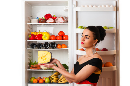 rijke vrouw: luxurious rich woman with cheese in the hands of the fridge