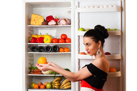 rijke vrouw: luxueuze rijke vrouw met oranje in handen en koelkast Stockfoto