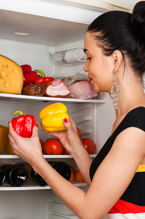 beautiful woman chooses peppers from the fridge photo