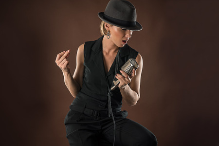 retro microphone: stylish woman in a hat with a retro microphone
