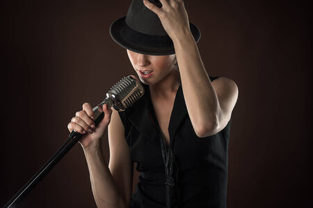 retro microphone: fashionable woman in a hat with a retro microphone