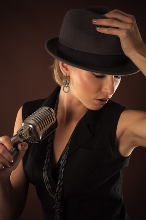 retro microphone: woman in a hat with a retro microphone Stock Photo