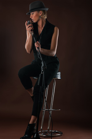 beautiful blond woman with a microphone sitting on bar chair photo