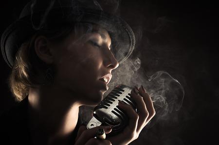 estudio de grabacion: Mujer cantante con el micr�fono retro Foto de archivo
