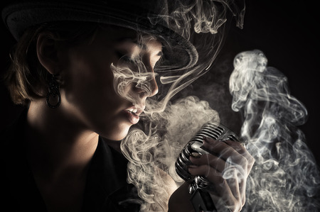 singer woman with retro microphone in smoke