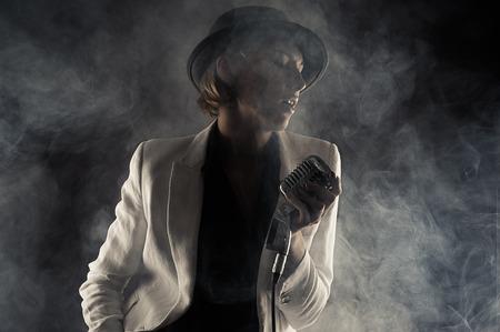 jazz singer: jazz singer woman with retro microphone in smoke Stock Photo