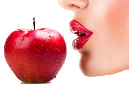 labios rojos: sexy mujer come la manzana roja, labios rojos y sensuales Foto de archivo