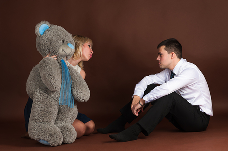 angry teddy: woman take away teddy bear of a young businessman Stock Photo
