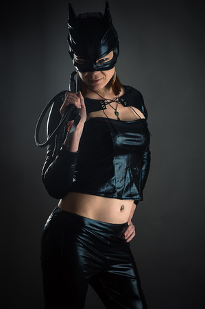 cat woman with a whip in hand isolated on black background