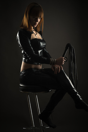 beautiful woman sitting on a bar stool with a whip in hand