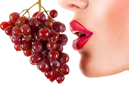 sexy woman eating red grapes, sensual red lips