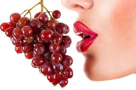 labios sensuales: Mujer atractiva que come las uvas rojas, labios rojos y sensuales