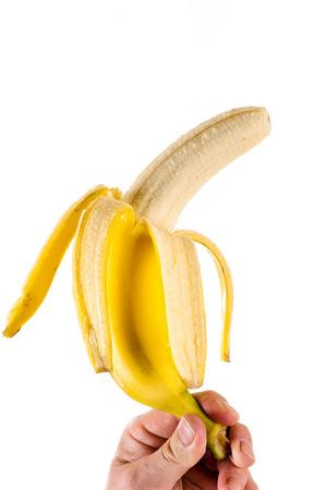 peeled banana: hand holding a peeled banana Stock Photo