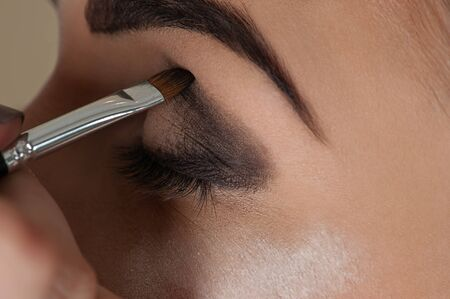 eyelids: makeup artist working with the eye make-up brush
