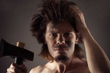hombre prehistorico: hombre prehistórico con un hacha en la mano Foto de archivo