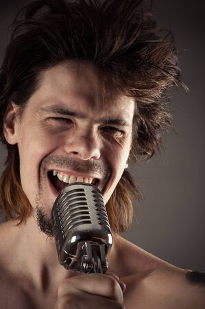 retro microphone: man with disheveled hair singing into retro microphone