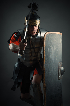 legionary: Roman legionary with sword and shield in the attack Stock Photo