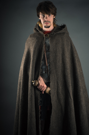 wandering man in woolen cape with a sword Stock Photo