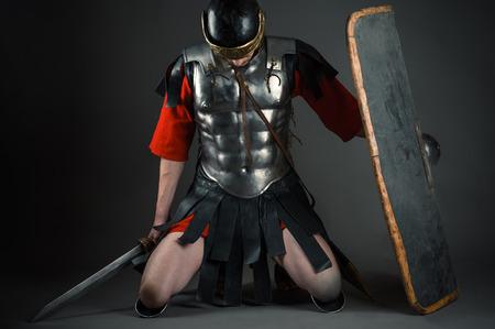 soldado: soldado cansado de rodillas con un escudo y una espada en las manos
