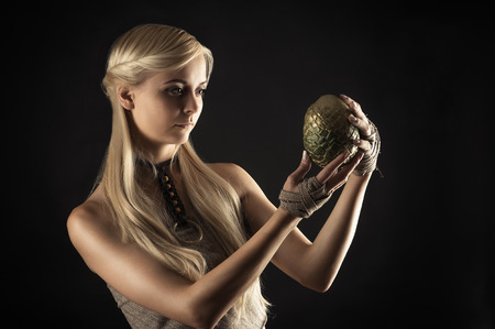 ttractive: ttractive woman in dress holding a dragon egg in hands