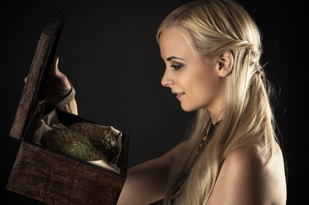 blond woman holding a box with eggs dragons
