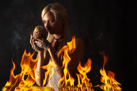 pensive woman with a dragon egg in the fire