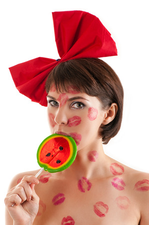 kissing lips: beautiful girl with a red bow and lollipop in mouth in lipstick kisses