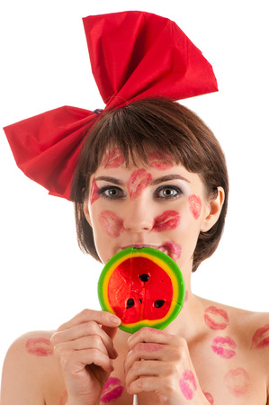 kissing lips: attractive girl with a red bow and lollipop in mouth in lipstick kisses Stock Photo